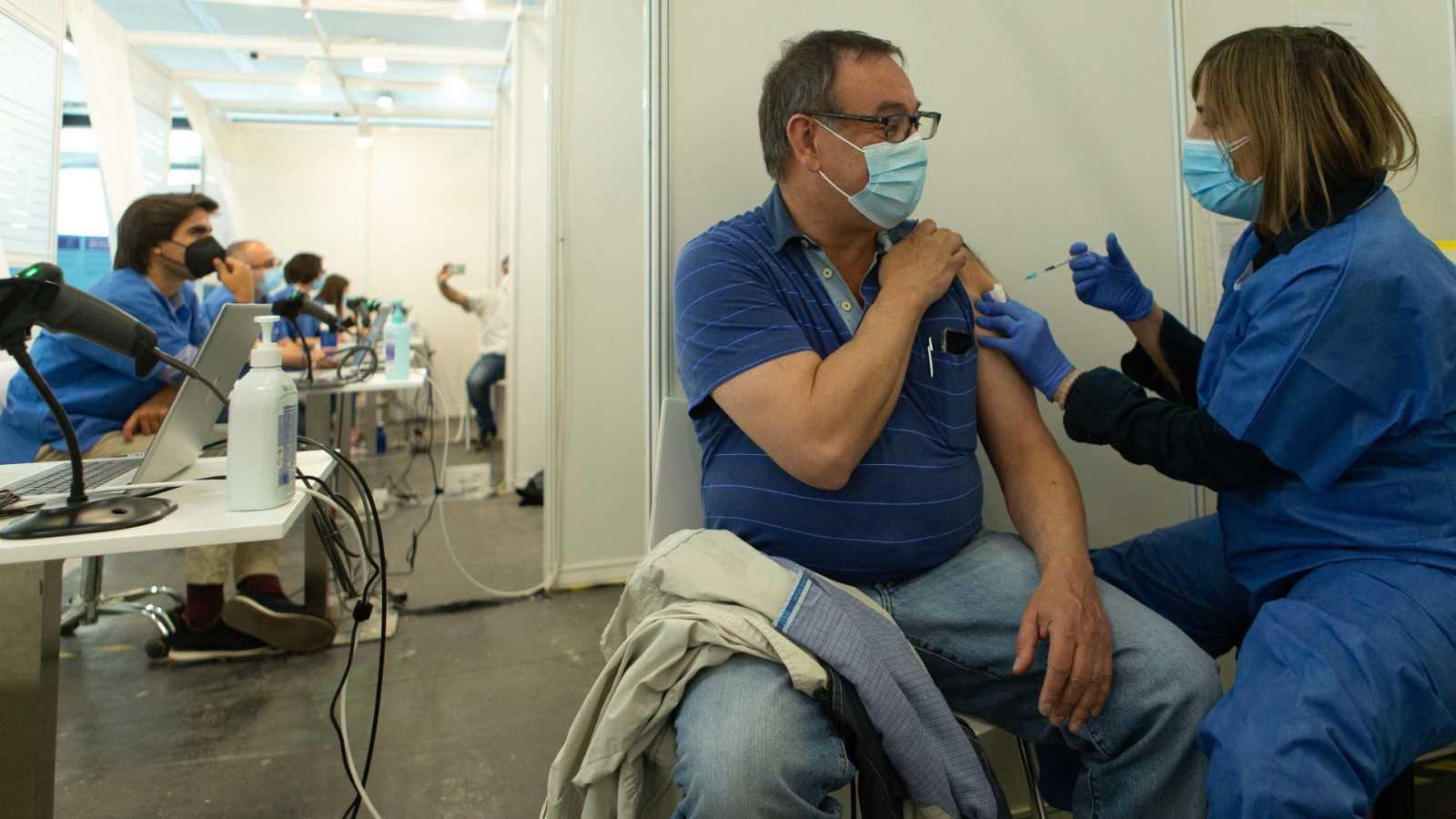 Una enfermera vacuna a un hombre contra la COVID-19 en el centro de vacunación de la Fira de Barcelona