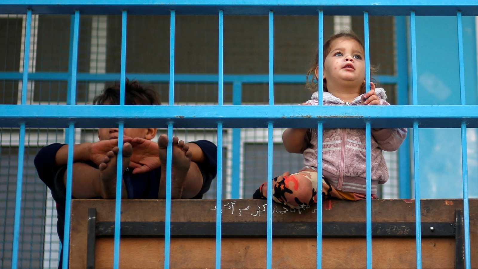 Un niño y una niña mirando por la ventana en el norte de Gaza