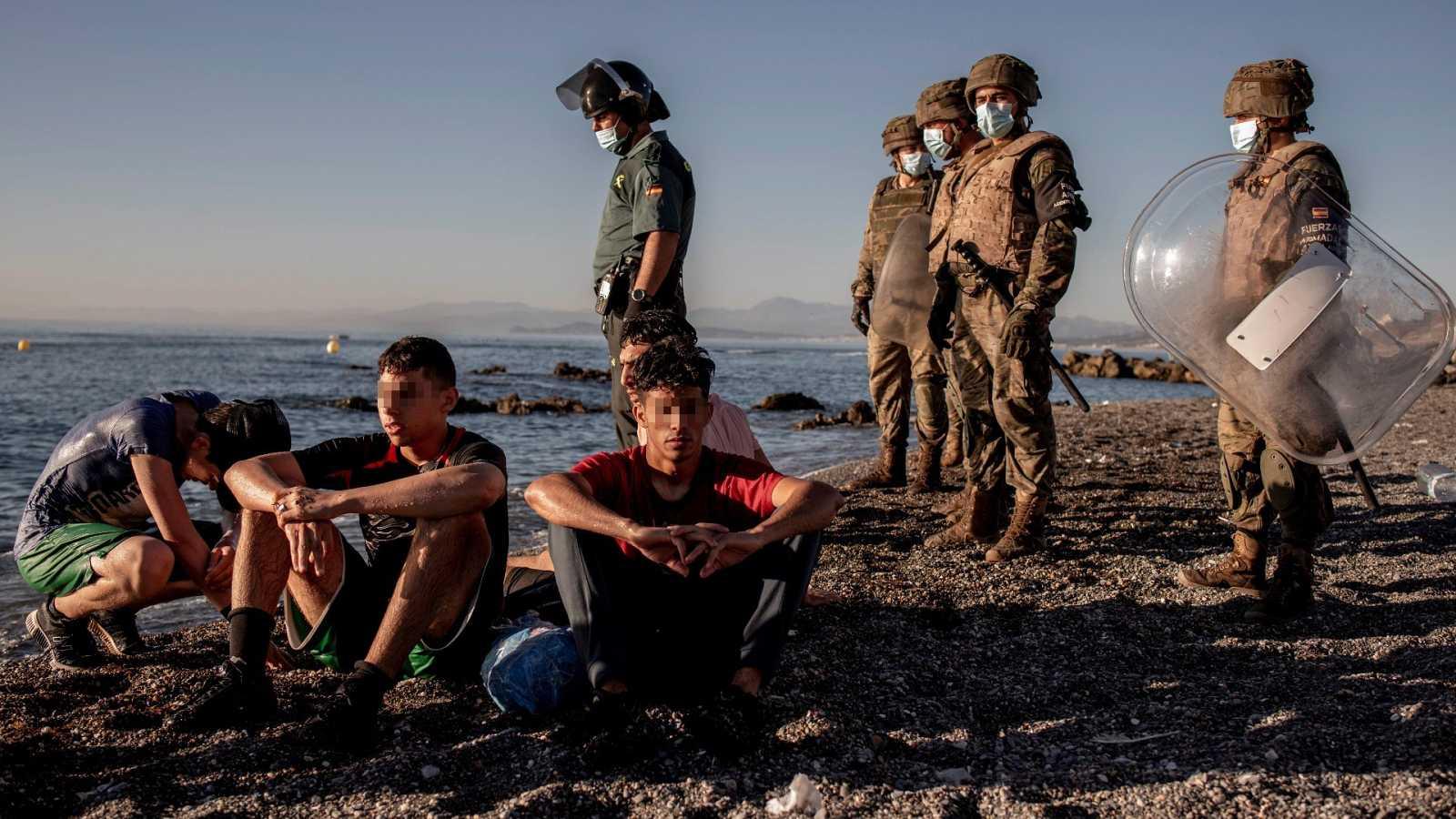 Miembros del ejército observan a un grupo de menores migrantes a su llegada a Ceuta el pasado mes de mayo