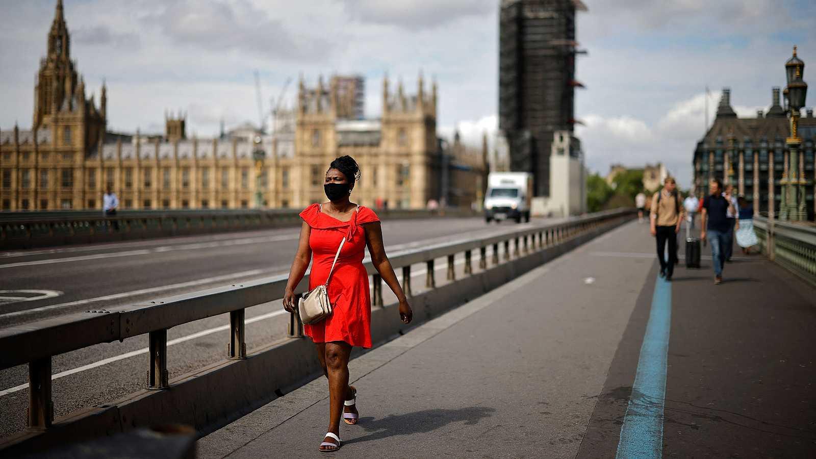 Una mujer cruza caminando el Puente de Westminster, en Londres.