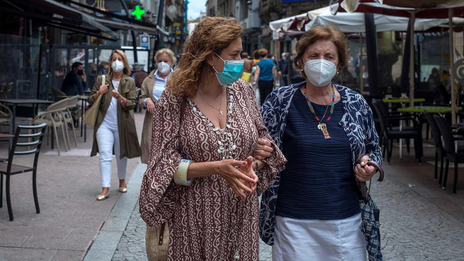 Dos mujeres caminan con mascarilla por la calle