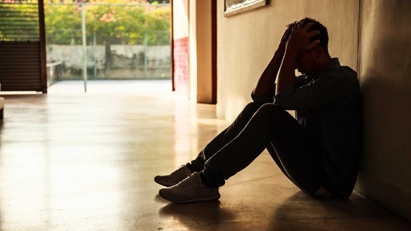 Un joven se sienta angustiado en los pasillos de un centro escolar.