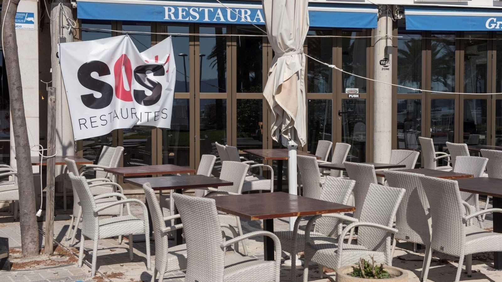 Un restaurante cerrado con la pancarta de la plataforma SOS Turismo en Pollença (Mallorca)