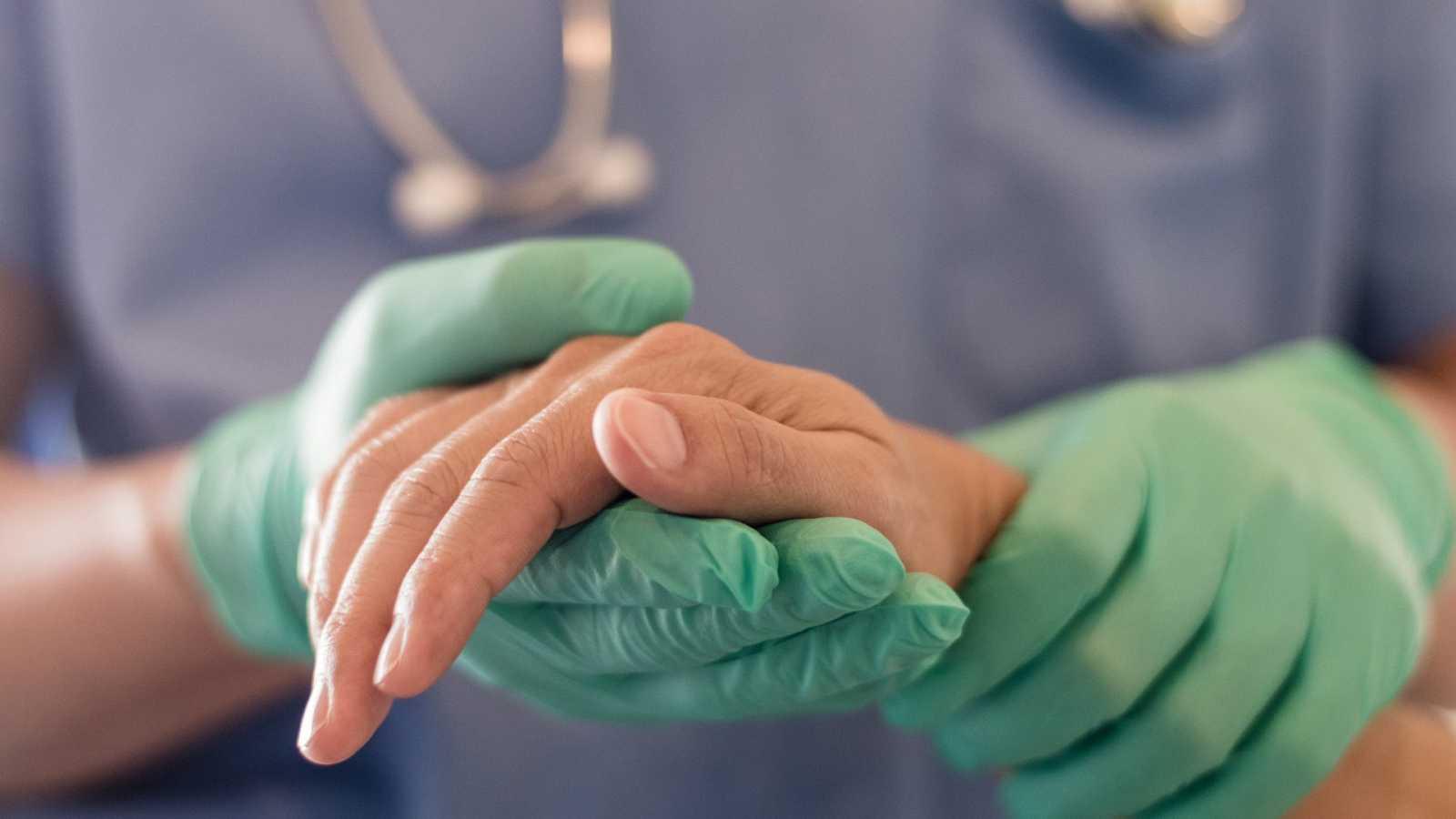 Cirujano, médico realiza operaciones quirúrgicas, anestesista o anestesiólogo sosteniendo la mano del paciente