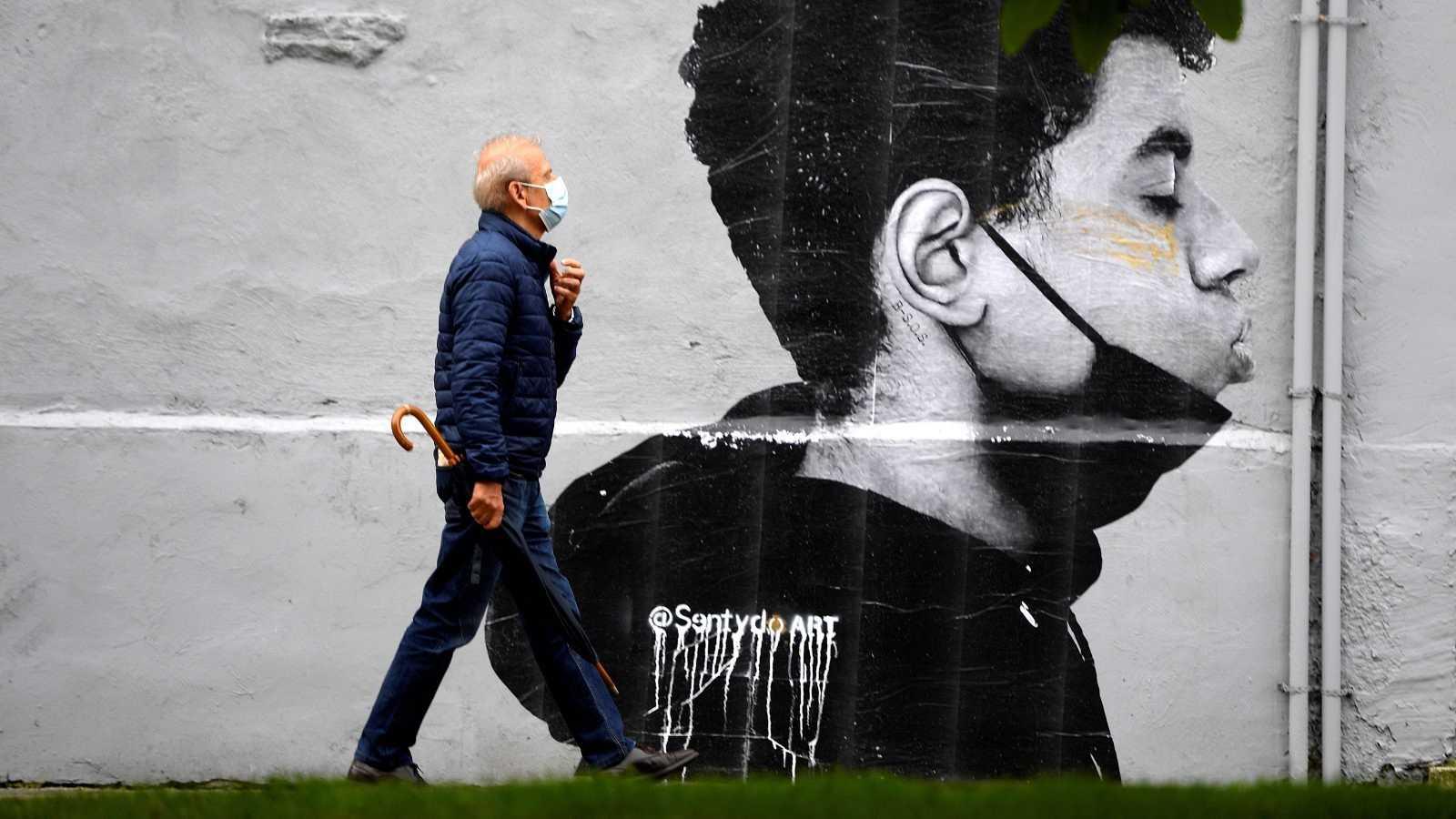 Un hombre con mascarilla camina delante de una obra del artista @Sentydo ART en Oviedo