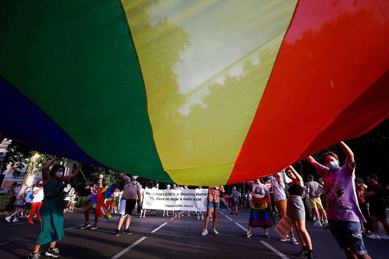 Participantes en la marcha del Orgullo LGTBI sostienen una enorme bandera del Orgullo.