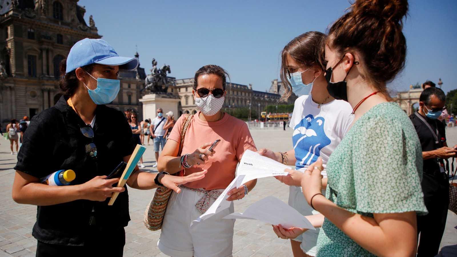 Un agente de seguridad comprueba los certificados COVID de las visitantes al Louvre, en París