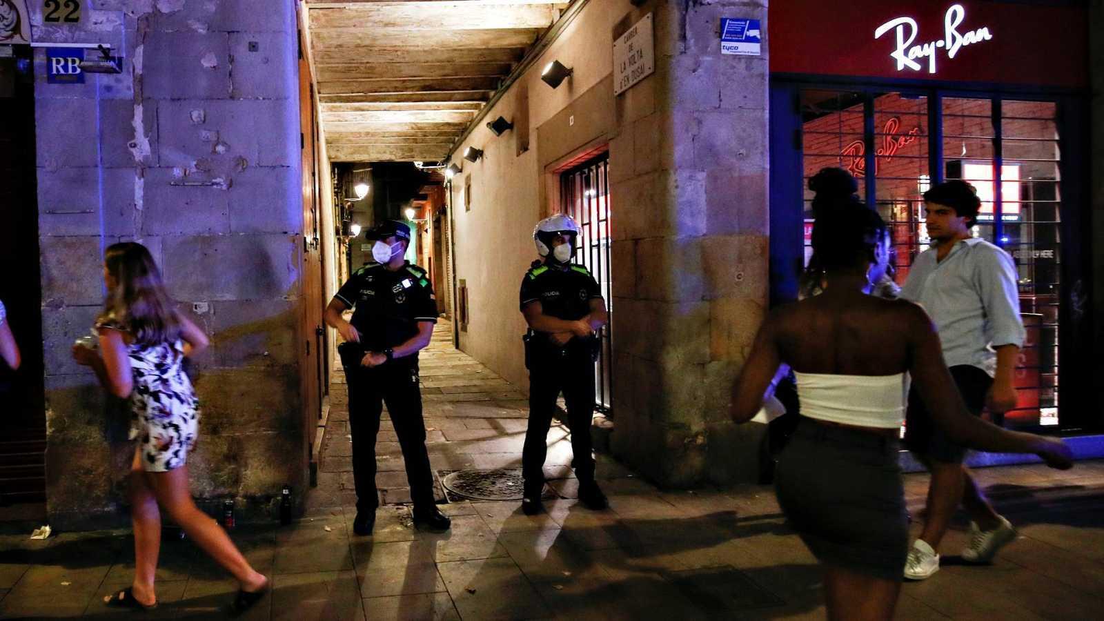Varios jóvenes sin mascarilla en una calle del centro de Barcelona