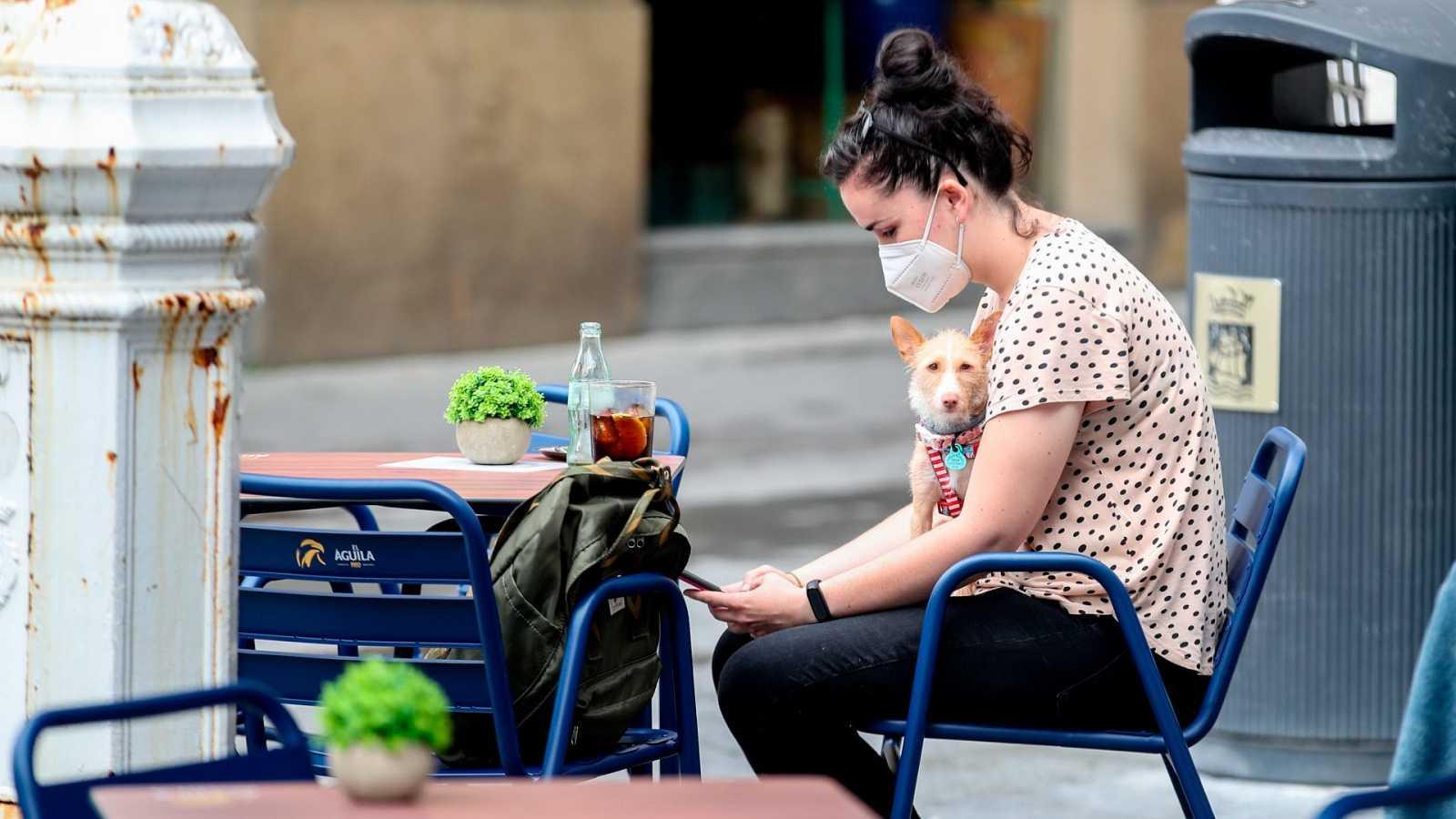 Una joven con mascarilla en una terraza de San Sebastián