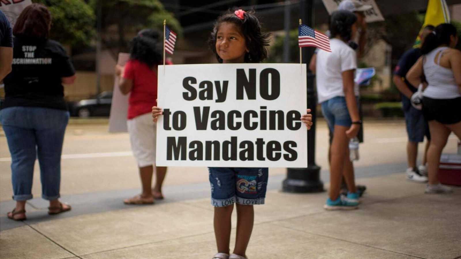 """Una niña sostiene un cartel en el que se lee """"di no al mandato de las vacunas"""" en una protestafuera del Hospital Metodista de Houston en Houston, Texas, EE.UU."""