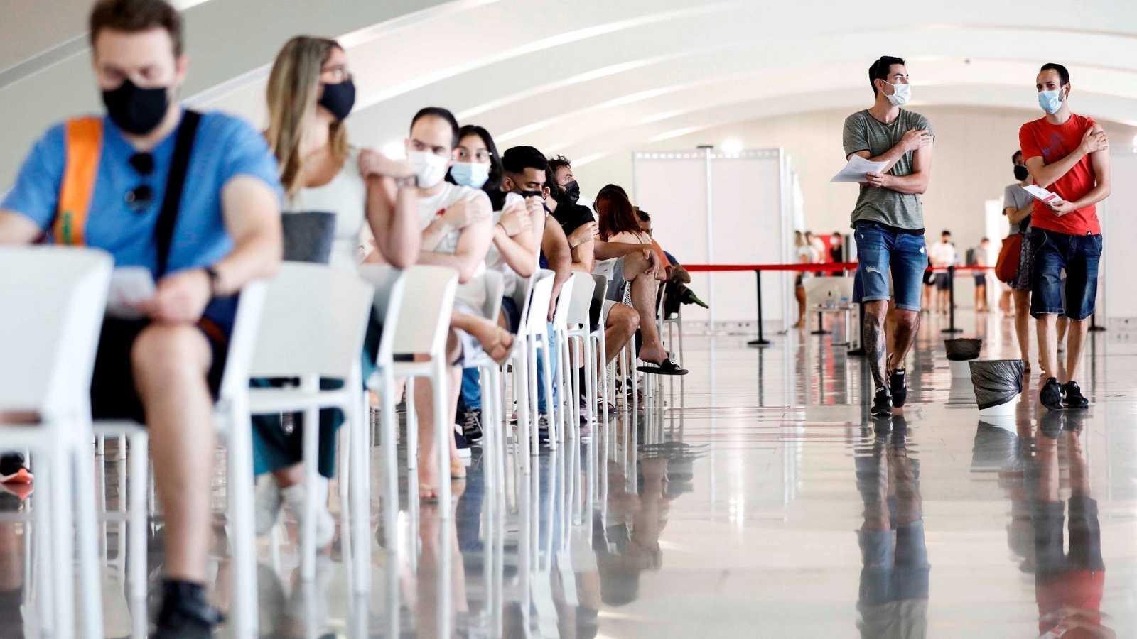 Varias personas esperan tras recibir su dosis de vacuna en la Ciudad de las Artes y las Ciencias de Valencia.