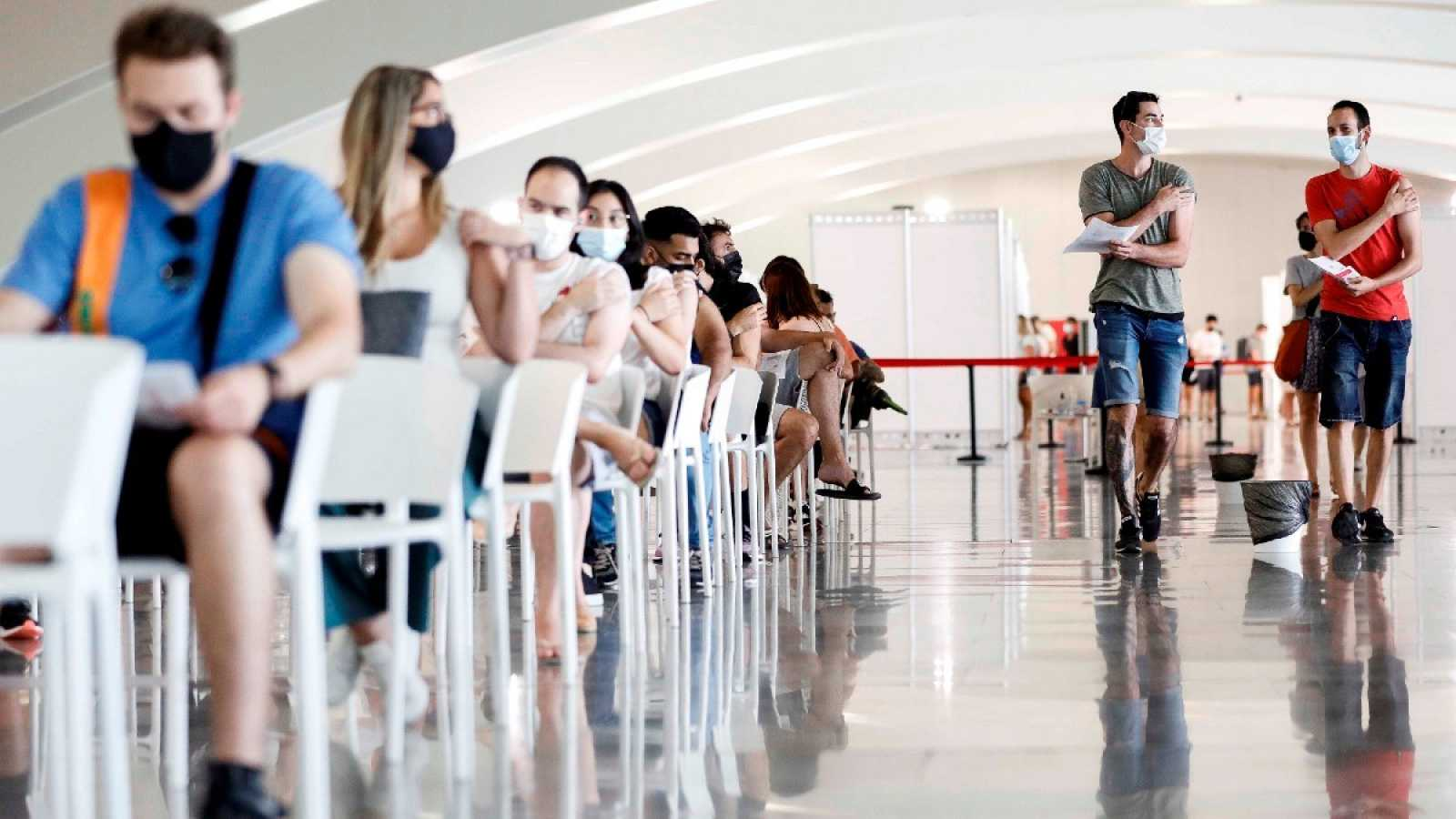 Varias personas esperan tras recibir la dosis de la vacuna en la Ciudad de las Artes y las Ciencias de Valencia