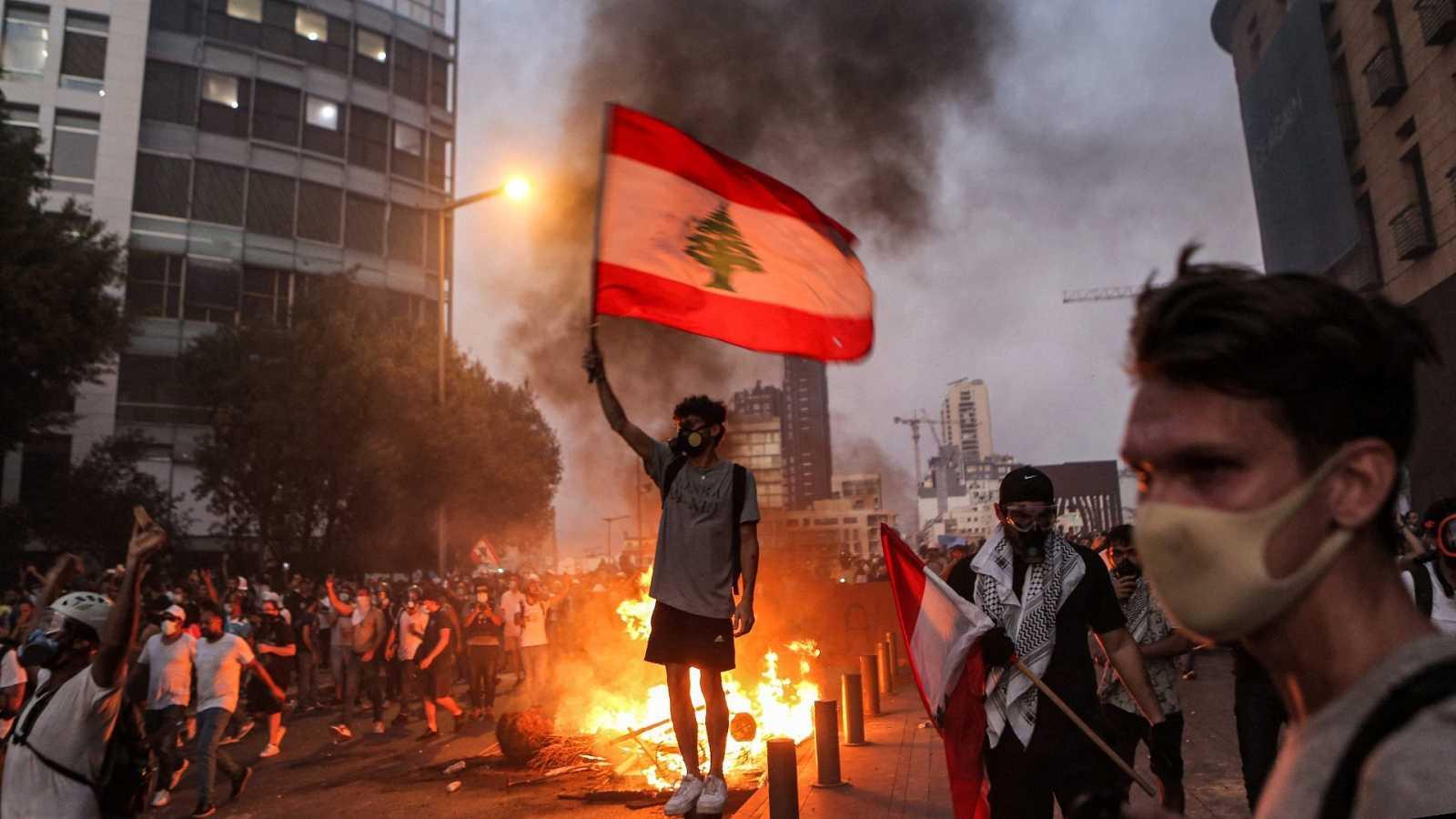 Un manifestante con una bandera nacional libanesa durante los enfrentamientos con el ejército y las fuerzas de seguridad
