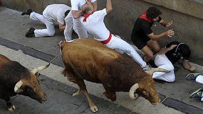 Un grupo de mozos cae ante un toro en los encierros de Sanfermines