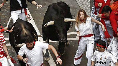 Una moza corre delante de los toros en Sanfermines