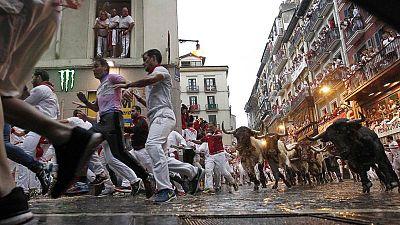 Corredores y toros, durante un encierro de Sanfermines