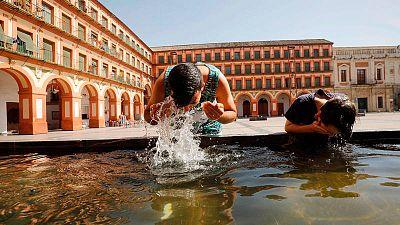 Unos niños se refrescan en una fuente de la Plaza de La Corredera de Córdoba