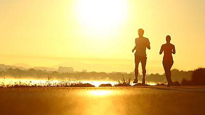 Un hombre y una mujer corren hacen deporte a la salida del sol