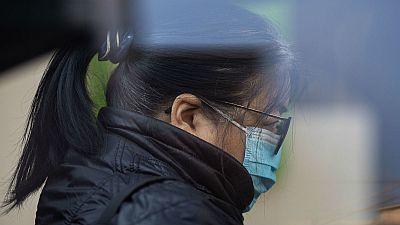 Con ya 132 muertos en China, una mujer hace cola para obtener mascarillas en una farmacia de Hong Kong.