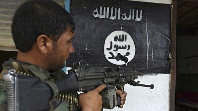 Un soldado empuña un arma a la entrada de una casa marcada por la bandera del Estado Islámico