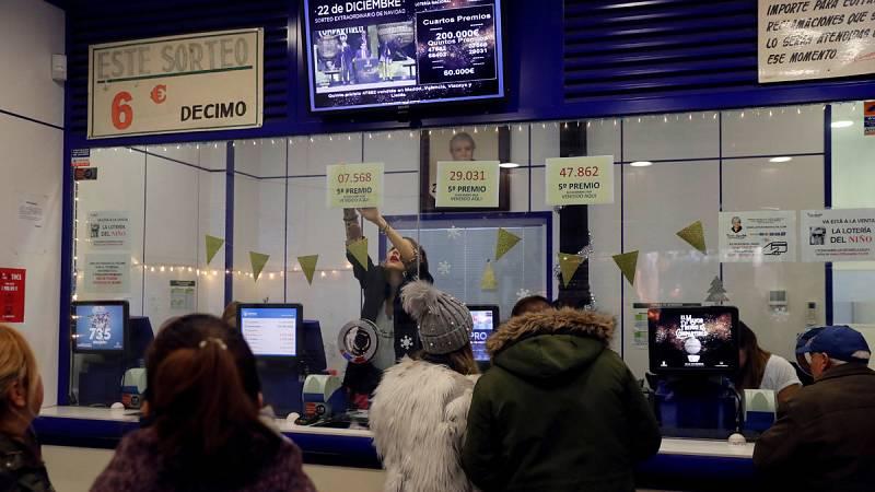 Personas comprueban sus boletos de Lotería del sorteo de Navidad, el 22 de diciembre de 2018