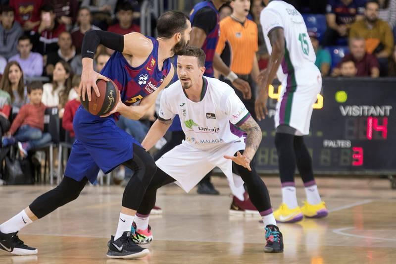 El base de Unicaja Josh Adams (d) defiende el avance de Pau Ribas (i), del Barça, en el partido correspondiente a la 13ª jornada de la Liga ACB en el Palau Blaugrana, en Barcelona.