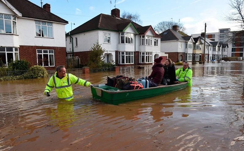 Algunos vecinos de Hereford, al oeste de Inglaterra, son rescatados de sus hogares en barcas por los servicios de emergencia durante las inundaciones.