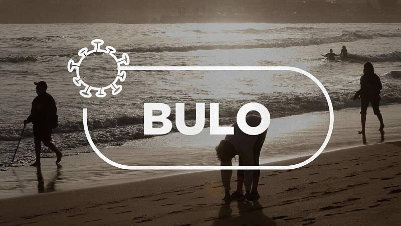 """Atardecer en una playa con gente que pasea manteniendo la distancia de seguridad bajo el sello con la palabra """"bulo"""""""