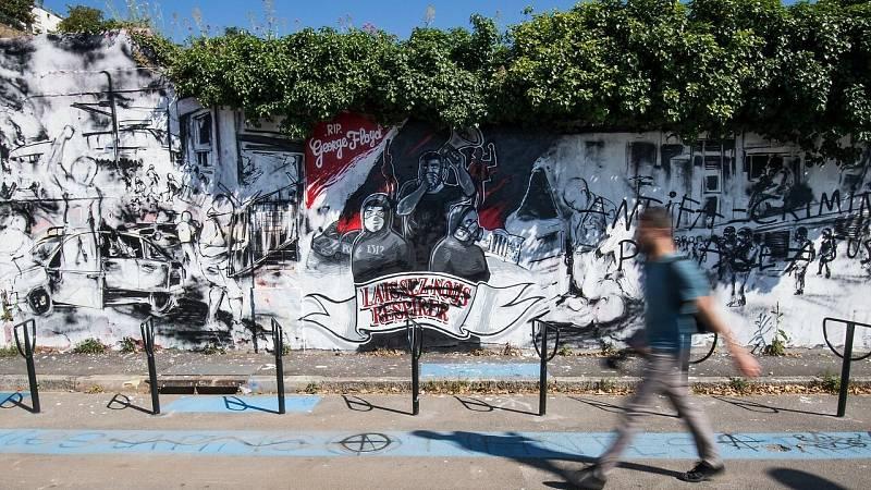 Un peatón camina ante un mural que homenajea al fallecido George Floyd