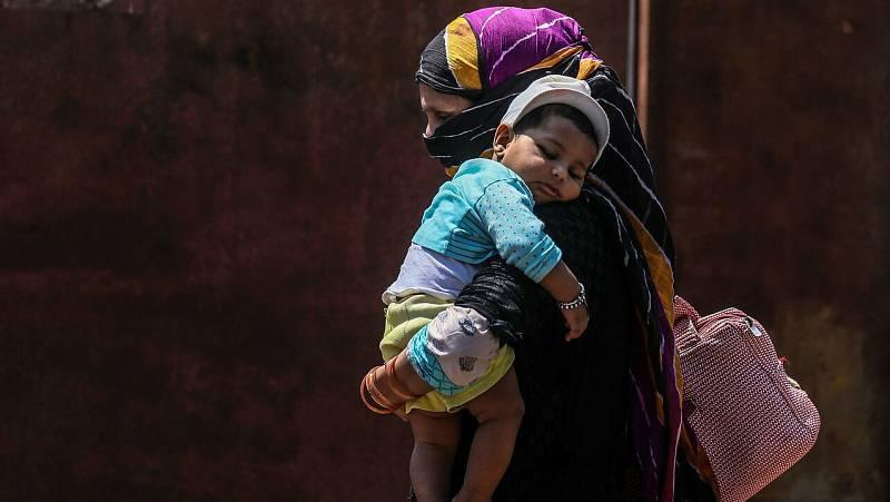 Una mujer carga con su bebe de camino a una estación de tren en Bombay (India).