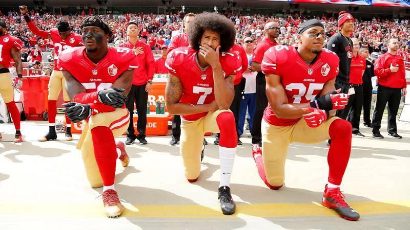 Colin Kaepernick (centro), arrodillado junto a otros dos jugadores mientras sonaba el himno de EE.UU. antes de un partido de la NFL de 2016