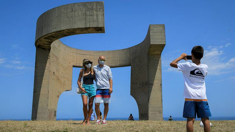 Dos turistas se fotografían ante el Elogio del Horizonte, de Eduardo Chillida, en Gijón.