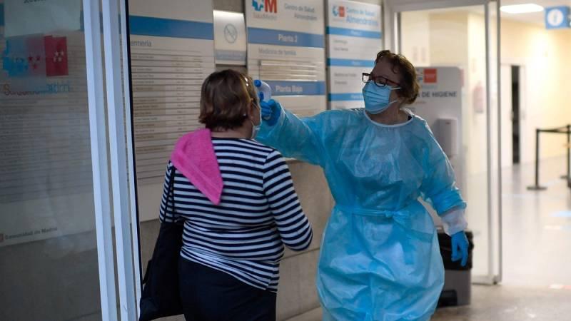 Una sanitaria toma la temperatura a una paciente en un centro de salud de Usera, Madrid.