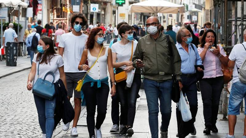 Un grupo de personas pasea por la calle con mascarilla