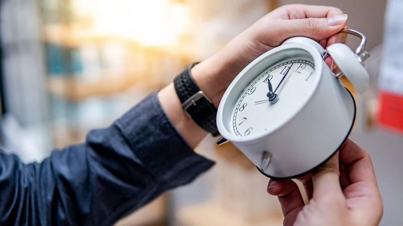 Un hombre cambia la hora en un reloj