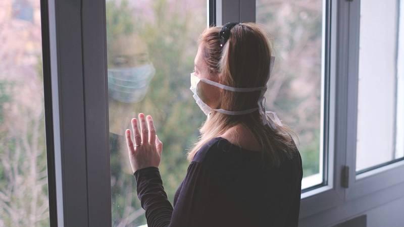Una paciente con mascarilla mira por la ventana