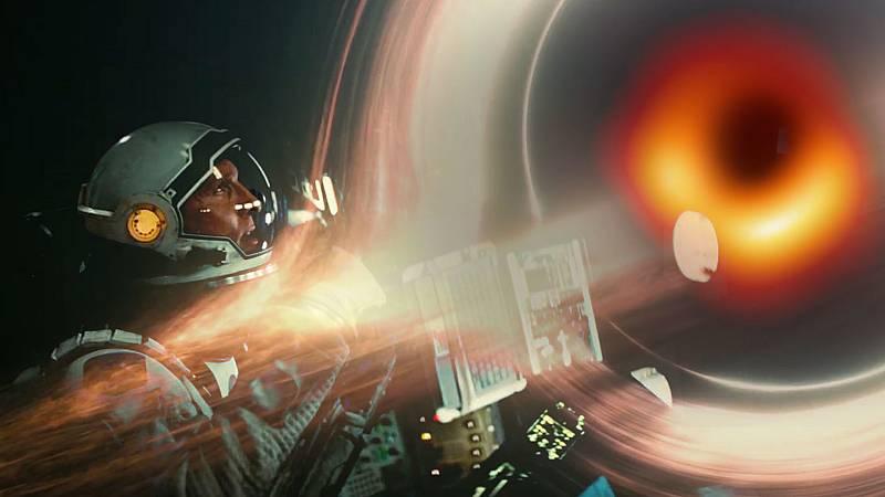Un agujero negro fotografiado en la realidad y su reproducción en Interstellar, sobreimpresionados en un fotograma de la película