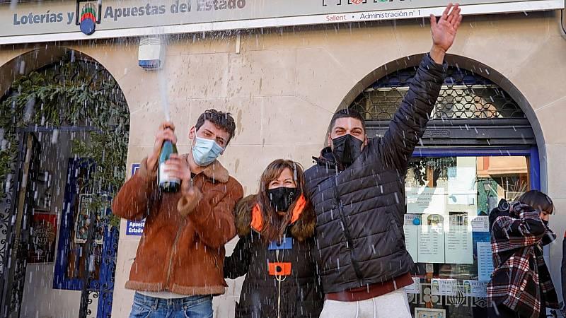 La encargada de la administración (c), uno de los agraciados (d) y algunos amigos celebran el primer premio de la Lotería del Niño vendido en la Administración número 1 de Sallent. v