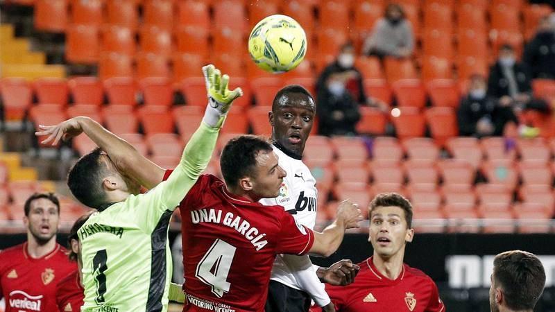 El defensa francés del Valencia Mouctar Diakhaby (c) trata de cabecear un balón durante el partido ante el Osasuna.