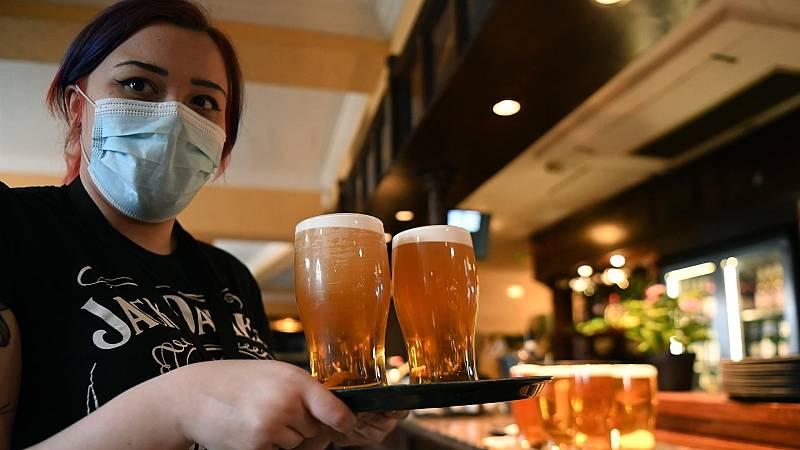 Una camarera con mascarilla en el interior de un restaurante