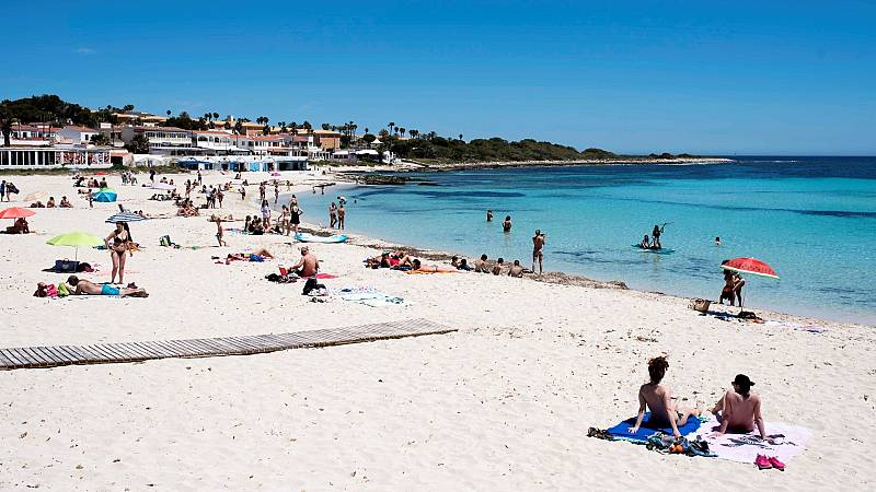 Turistas disfrutan de un día en la playa de Punta Prima, en Menorc