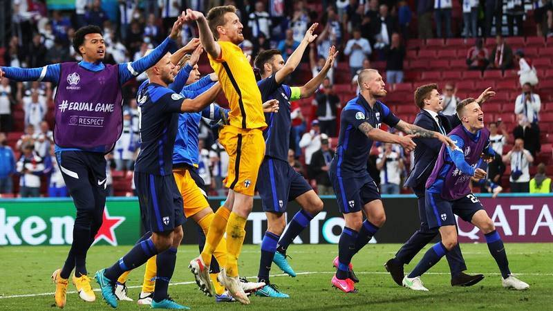 Los jugadores de la selección de Finlandia celebran la victoria sobre Dinamarca con sus aficionados.
