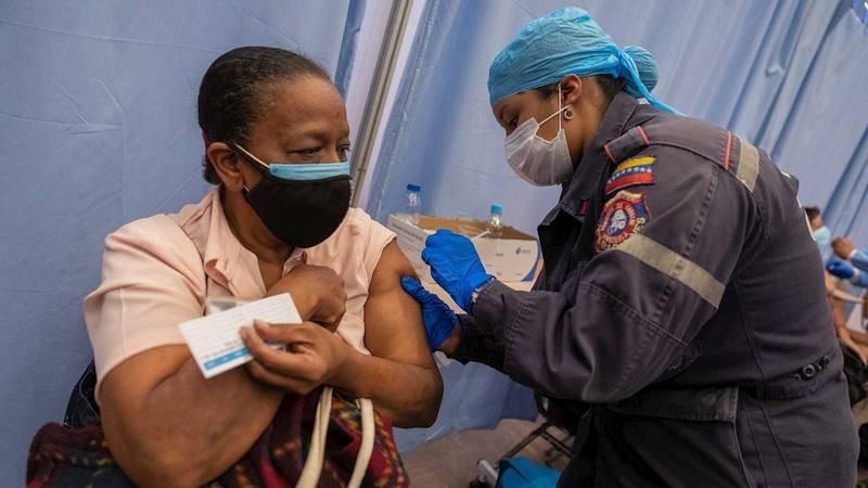 Una funcionaria aplica una dosis de la vacuna china Vero Cell a una mujer en Caracas