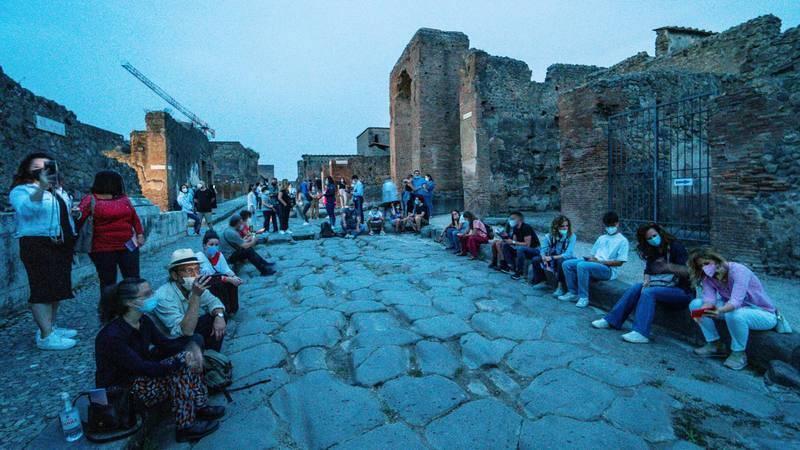 Grupo de turistas, todos con mascarilla, en Pompeya, Italia