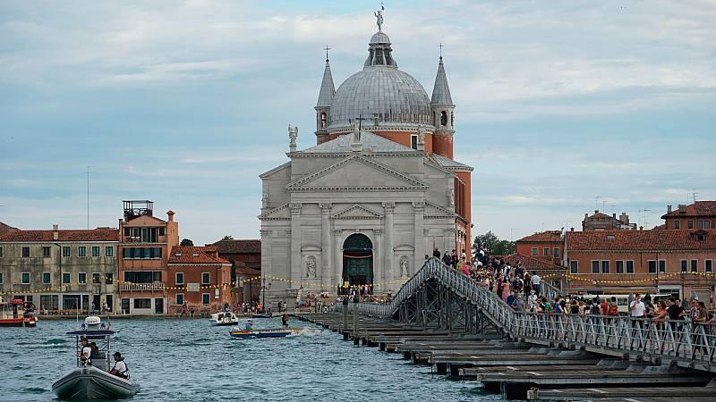 Peregrinos y turistas cruzan el puenteque conecta las orillas opuestas del Canal de la Giudecca, para llegar a la Iglesia del Redentor, en vísperas de la Festa del Redentore en Venecia, Italia