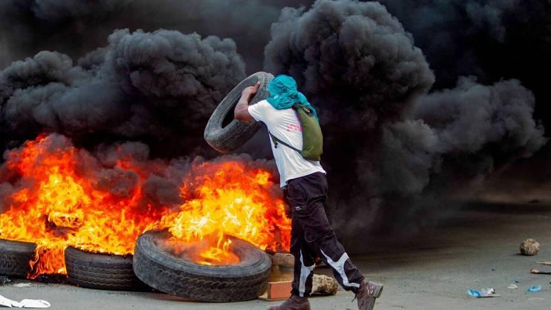 Un hombre arroja una llanta a una barricada en llamas durante una jornada de protestas, en Cap-Haitien (Haití).