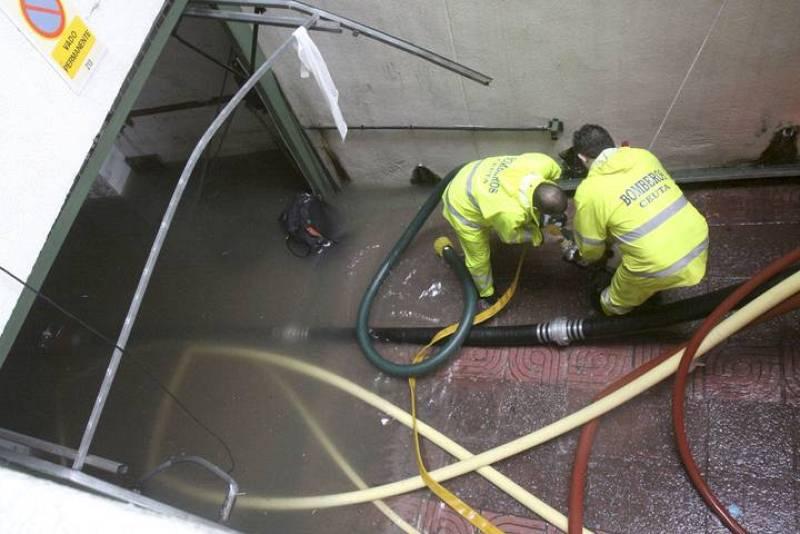 Dos bomberos quitan el agua de un bajo en Ceuta