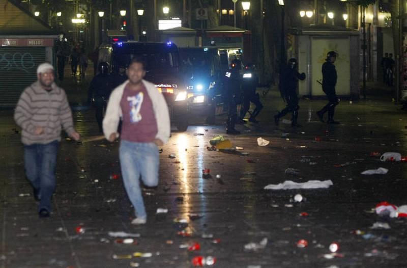 Algunas personas corren por las calles de Barcelona para escapar de los Mossos d' Esquadra.