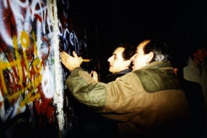 Esta foto difundida por el presidente francés a través de Facebook en la que aparece en la caída del Muro de Berlín -cuando al parecer estuvo tan solo unos días después- ha provocado un aluvión de parodias.