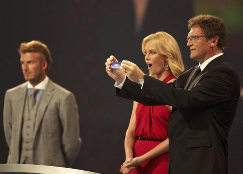 El secretario general de la FIFA, Jerome Valcke, sostiene la papeleta de Francia mientras Charlize Theron y Beckham observan.